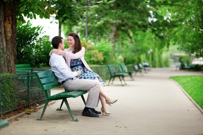 Het dateren van paar die op een bank in een Parijse park koesteren stock afbeeldingen