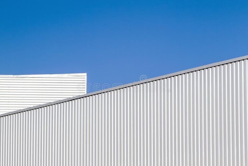 Het de golfmuur en dak van het bladmetaal tegen blauwe hemel Modern pakhuis of opslag Industrieel kijk openlucht Digitaal royalty-vrije stock foto