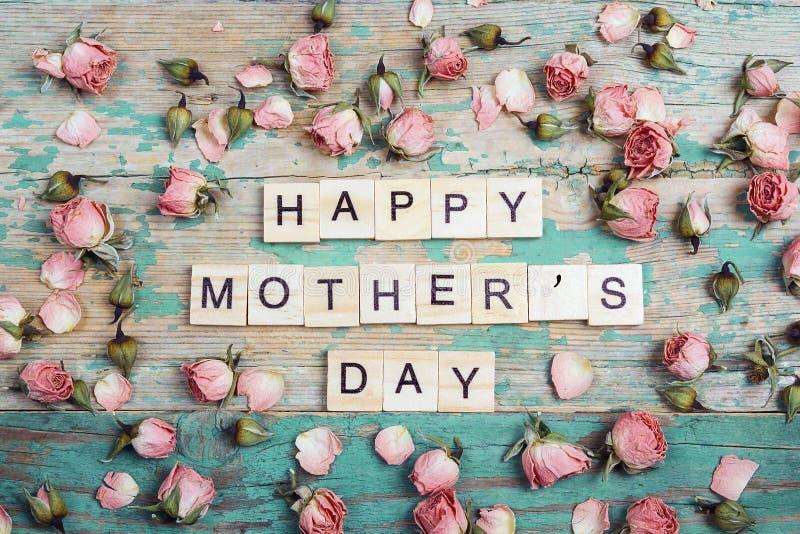 Het de groetbericht van de moedersdag met kleine droge rozen na op oud streeft stock fotografie