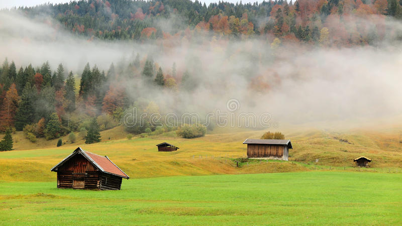 Het de herfstlandschap van Beiers platteland met grasgebied en de houten schuren in ochtend vertroebelen stock fotografie