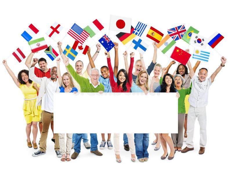 Het de Internationale Vlaggen en Aanplakbiljet van de mensenholding royalty-vrije stock foto