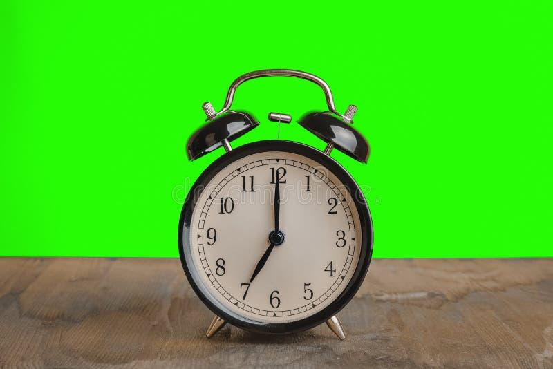 Het de klok van ` s zeven o ` reeds, tijd om voor ontbijt, uitstekende oude zwarte metaalwekker te ontwaken stock fotografie