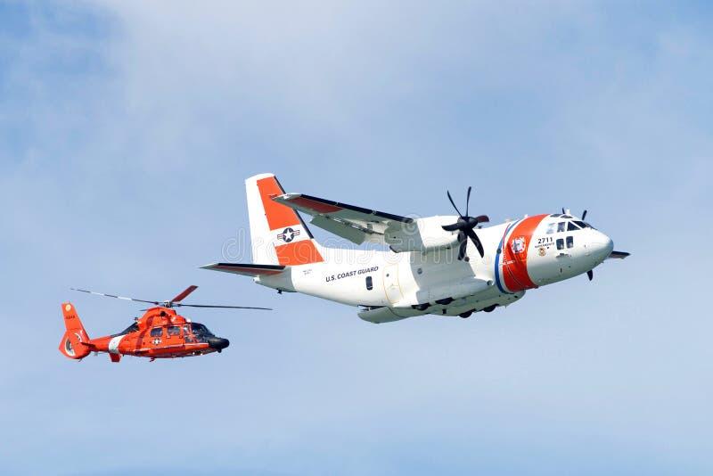 Het de Kustwachthelikopter en vliegtuig die in lucht vliegen tonen stock foto