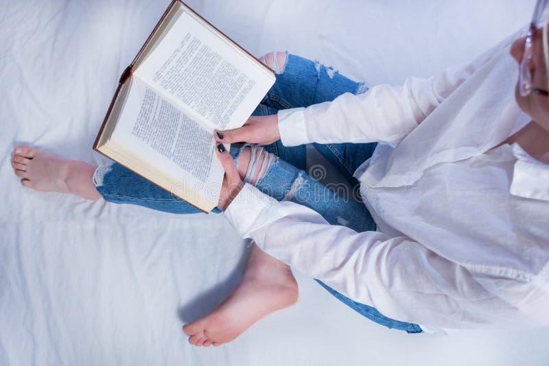 Het de lezingsboek van het studentenmeisje in comfortabel bed en de holding boeken op benen met naakte voeten stock foto