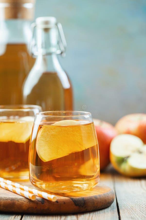Het de organische cider of sap van Apple op een houten lijst met exemplaarruimte Twee glazen met drank en de herfstbladeren op pl royalty-vrije stock foto's