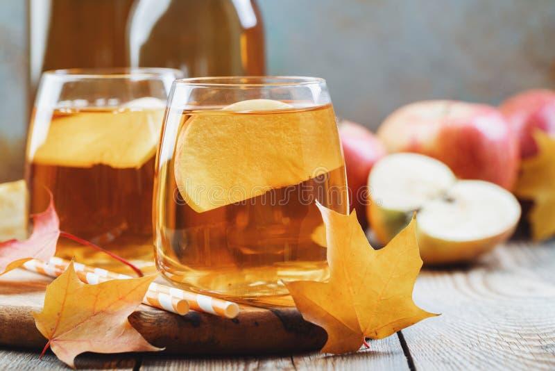 Het de organische cider of sap van Apple op een houten lijst Twee glazen met drank en de herfstbladeren op rustieke achtergrond stock afbeelding