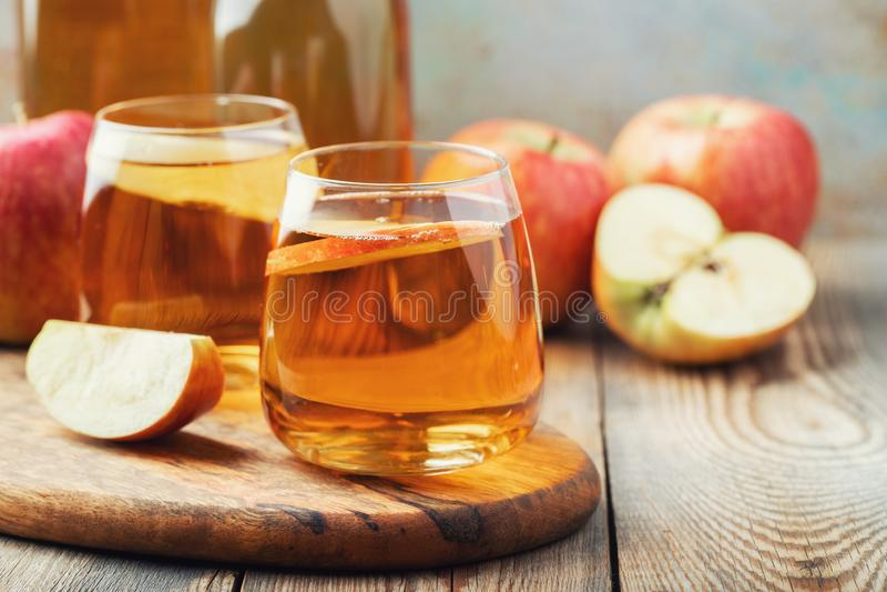 Het de organische cider of sap van Apple op een houten lijst Twee glazen met drank en de herfstbladeren op rustieke achtergrond stock foto's