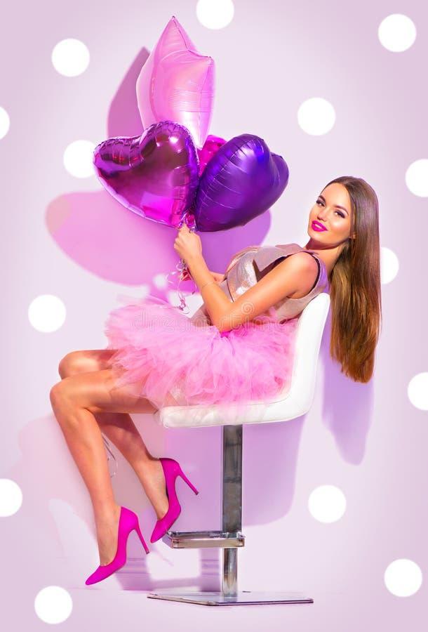 Het de partijmeisje van de schoonheidsmannequin met hart gaf luchtballons het stellen gestalte, zittend op stoel Verjaardagsparti stock afbeeldingen