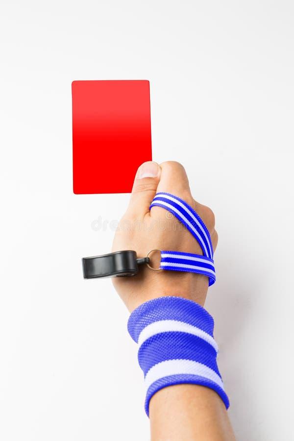 Het de scheidsrechtershand en fluitje tonen kaart aan speler stock foto's