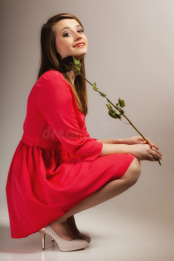 Het de tienermeisje van de maniervrouw in rode toga met droog nam toe stock afbeelding