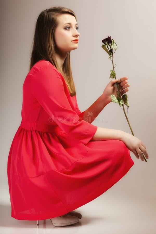 Het de tienermeisje van de maniervrouw in rode toga met droog nam toe stock foto