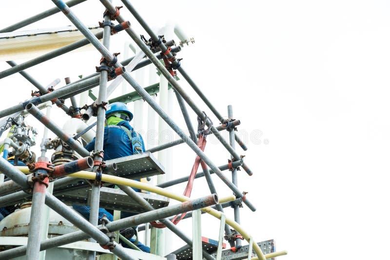 Het de veiligheidsgordelwerk van de arbeidersslijtage bij hoogte op steiger royalty-vrije stock afbeelding