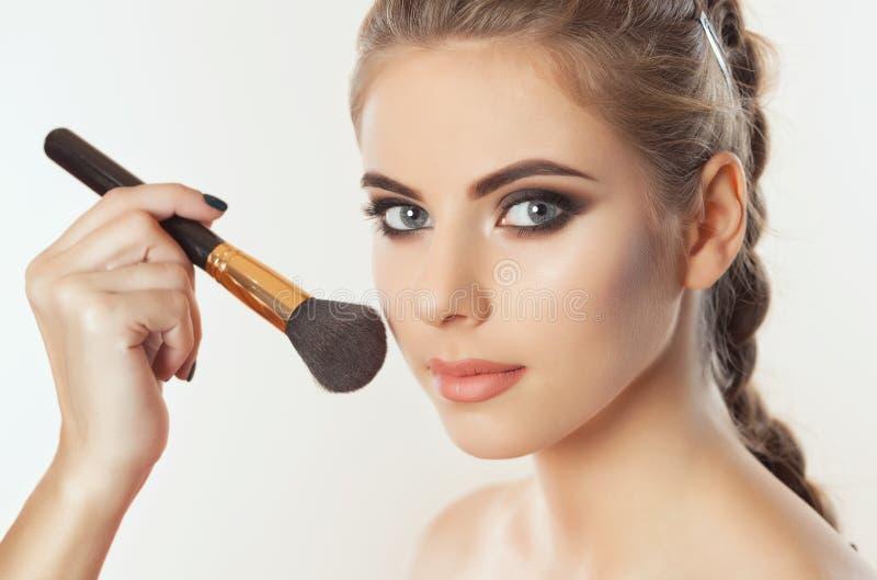Het de vervenpoeder van de Make-upkunstenaar op het gezicht van het meisje, voltooit samenstelling in de schoonheidssalon stock foto's