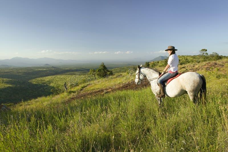 Het de vrouwelijke horseback ruiter en paard berijden het overzien van Lewa-het Wildmilieubescherming in Noord-Kenia, Afrika royalty-vrije stock fotografie
