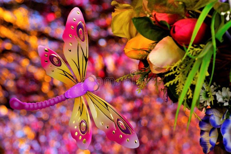 Het de zomerconcept, libel vliegt op een boeket van bloemen, op een regenboog bokeh achtergrond De decoratie van de bloementuin h stock afbeelding