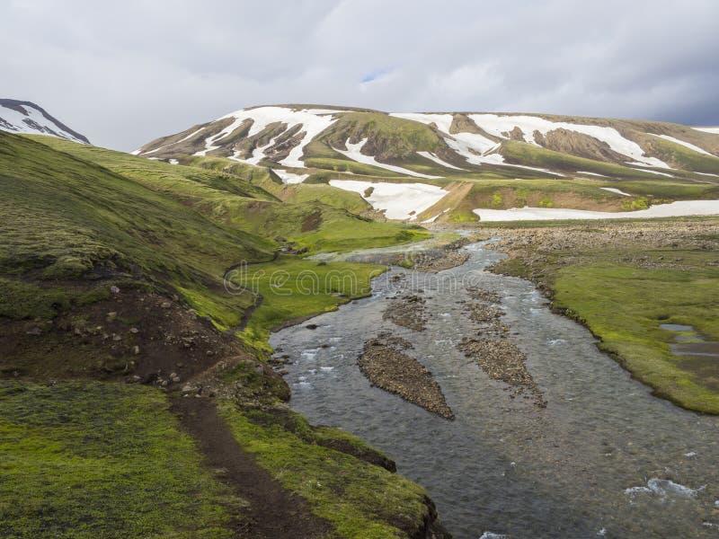 Het de zomerlandschap met kleurrijke groene en oranje mosweide met de hete lentes en sneeuw behandelde binnen rhyolit bergen royalty-vrije stock afbeeldingen