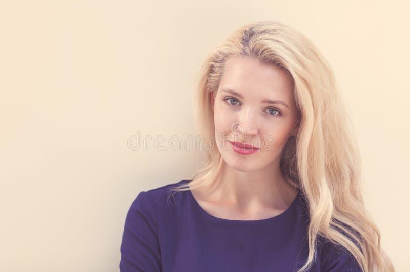 Het de zomerportret van jonge mooie blonde vrouw in het blauwe kleding stellen dichtbij de muur en heeft pret Gestemd in warme kl stock afbeelding