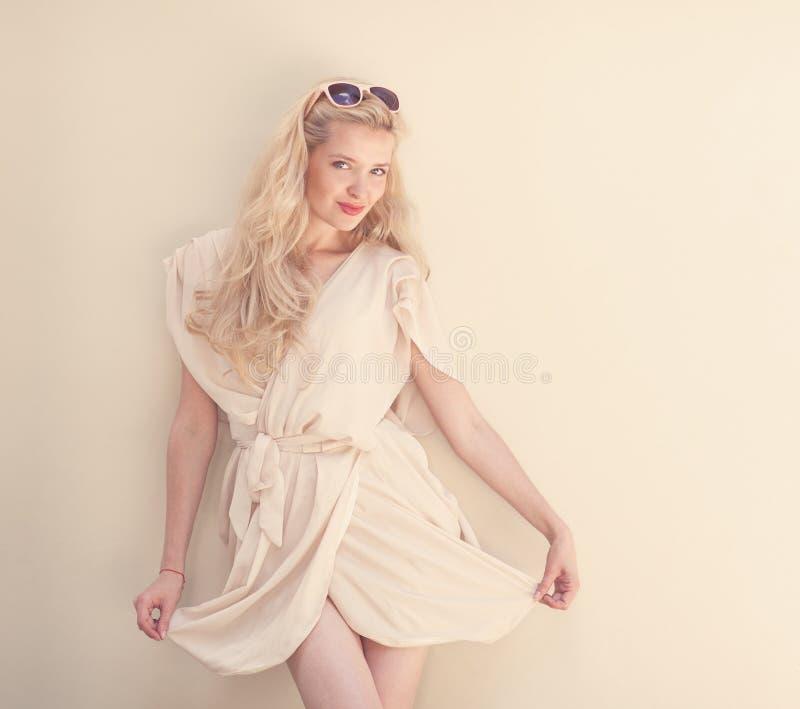 Het de zomerportret van jonge mooie blonde vrouw in het witte kleding stellen dichtbij de muur en heeft pret Gestemd in warme kle royalty-vrije stock fotografie