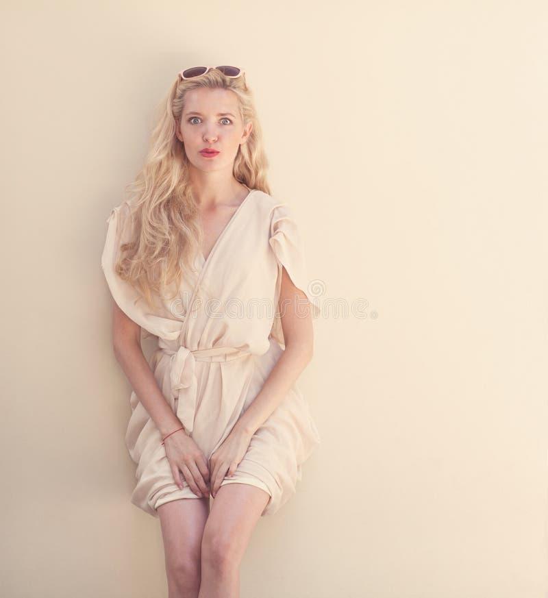 Het de zomerportret van jonge mooie blonde vrouw in het witte kleding stellen dichtbij de muur en heeft pret Gestemd in warme kle royalty-vrije stock afbeelding