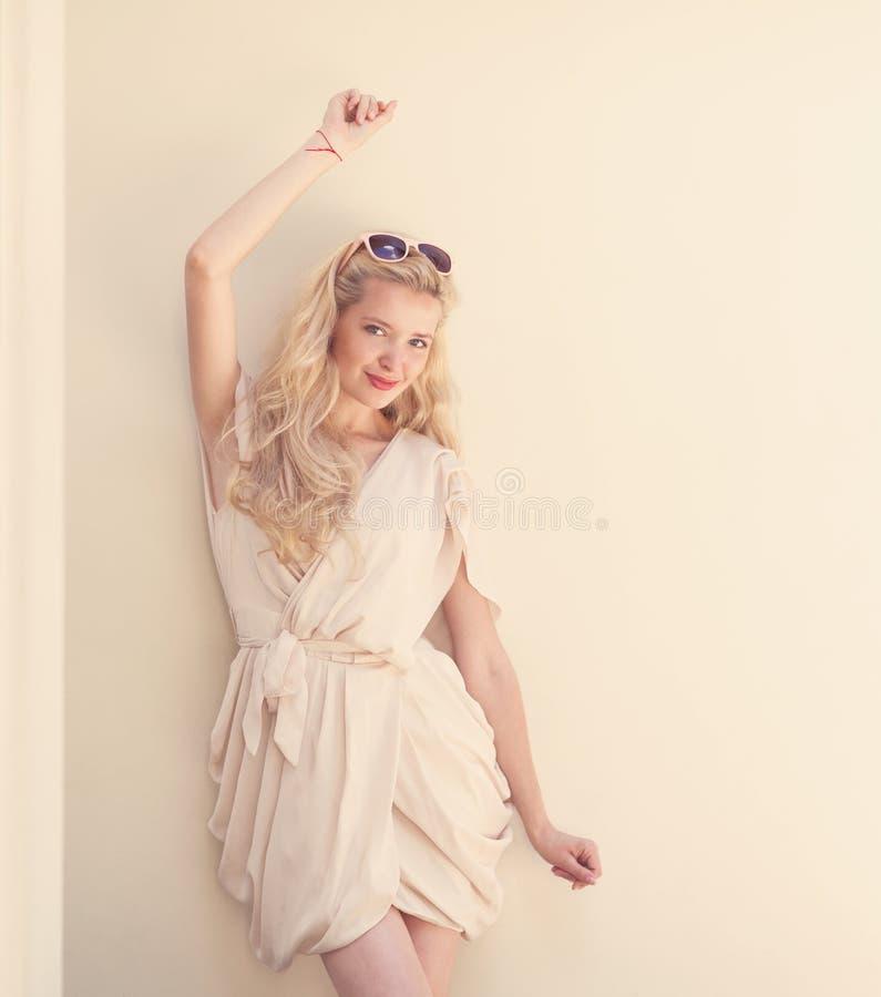 Het de zomerportret van jonge mooie blonde vrouw in het witte kleding stellen dichtbij de muur en heeft pret Gestemd in warme kle stock foto's