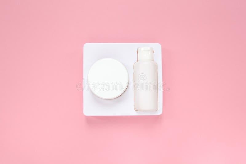 Het de het de zorgsysteem, room en tonicum van de huishuid in witte verpakking op pastelkleur roze achtergrond, vlakte lagen Het  stock fotografie
