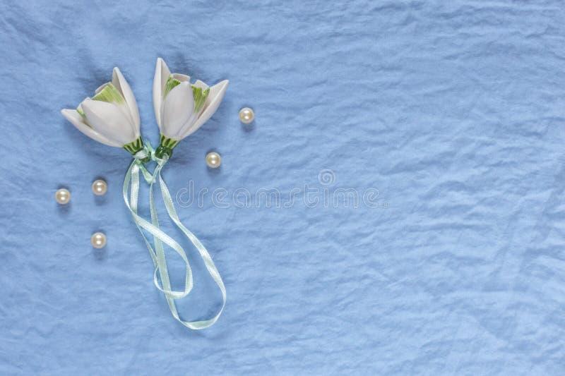 Het decor van het huwelijk Witte ceramische bloemen, parels op een blauwe stoffenbedelaars royalty-vrije stock afbeelding