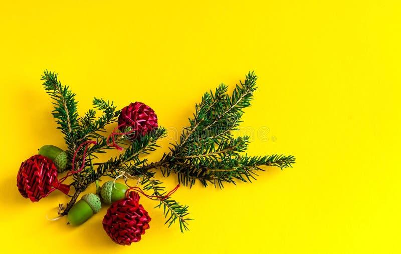 Het decor van Kerstmis Decoratieve nette takken en rode ballen op gele achtergrond, concept Nieuwjarenvakantie, close-up, royalty-vrije stock foto