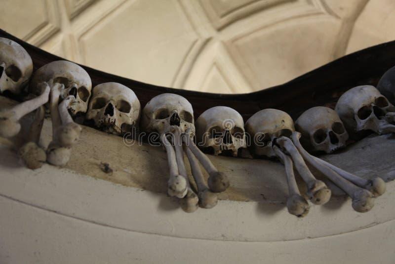 Het decor van menselijke schedels en beenderen in een ossuarium van Gotisch van de Kerk van de Begraafplaats van Alle Heiligen in stock foto