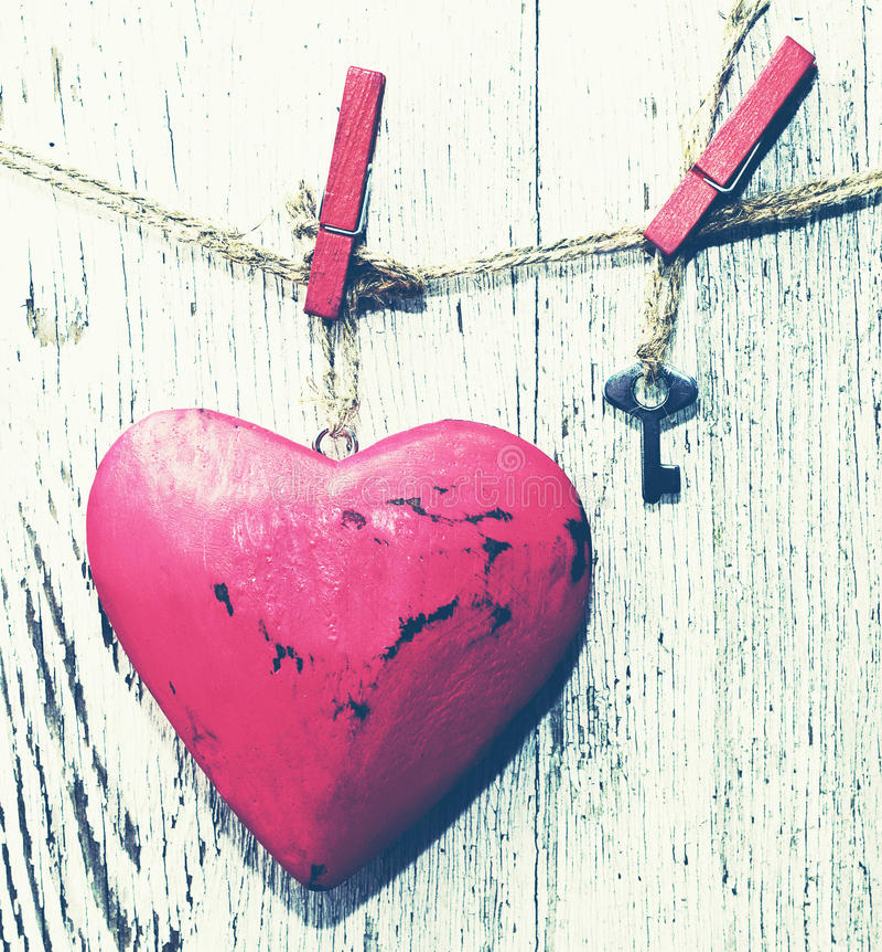Het decoratieve rode hart en het kleine metaal sluiten op een kabel tegen de achtergrond van een oude witte raad royalty-vrije stock foto