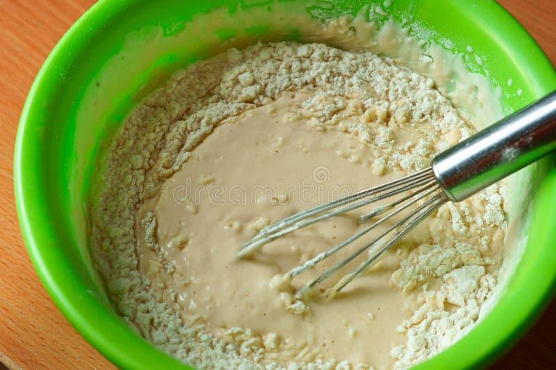 Het deeg in een kom en zwaait voor zich het mengen, vloeibaar deeg voor pannekoeken, klaar deeg voor bakselpannekoeken royalty-vrije stock afbeeldingen