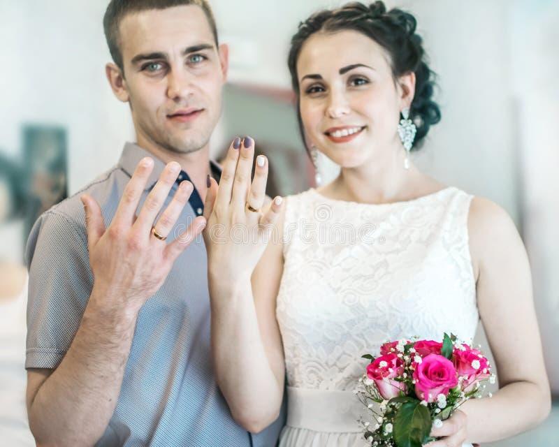 Het Defocusedportret van mooie jonge paar vrouwelijke vrouw met klein huwelijksroze bloeit rozenboeket en mannelijke echtgenoot d royalty-vrije stock fotografie