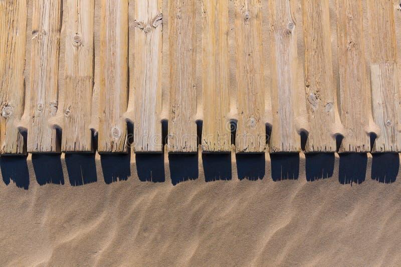 Het dek van het pijnboomhout doorstaan in de textuur van het strandzand stock foto's