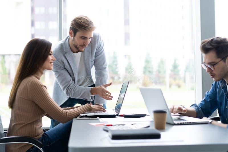 Het delen van adviezen Groep jonge moderne mensen die in slimme vrijetijdskleding zaken bespreken terwijl het werken in creatief royalty-vrije stock afbeeldingen