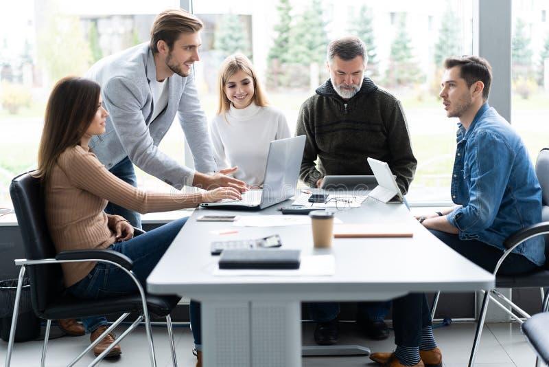Het delen van adviezen Groep jonge moderne mensen die in slimme vrijetijdskleding zaken bespreken terwijl het werken in creatief stock foto