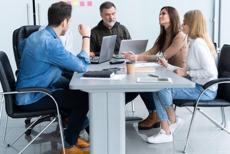 Het delen van adviezen Groep jonge moderne mensen die in slimme vrijetijdskleding zaken bespreken terwijl het werken in creatief stock foto's