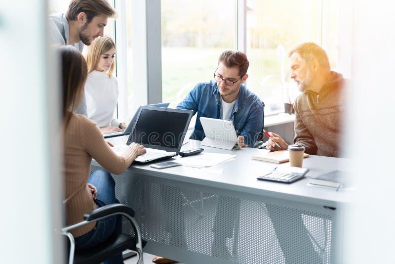 Het delen van adviezen Groep jonge moderne mensen die in slimme vrijetijdskleding zaken bespreken terwijl het werken in creatief royalty-vrije stock foto's