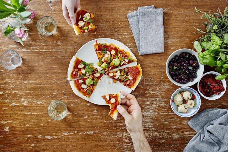 Het delen van en het eten van gezonde organische pizza bij diner stock afbeelding