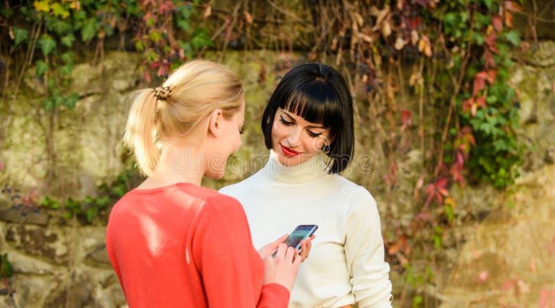 Het delen van verbinding Twee vrouwen die met smartphone in openlucht communiceren Sociaal netwerkenconcept Moderne technologie H stock afbeelding