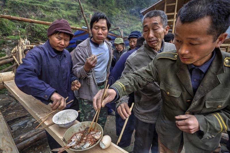 Het delen van voedsel op een landelijke viering, plaatselijke bevolkinglandbouwers, China stock foto's