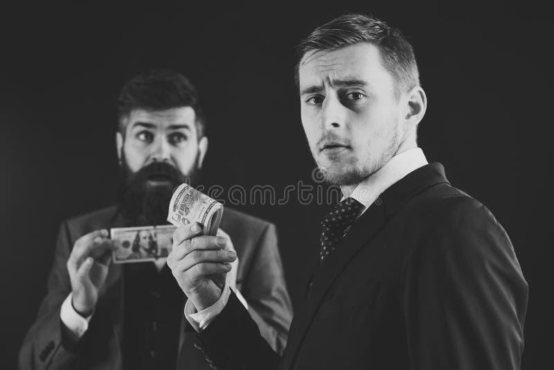 Het delen van winstenconcept Vergadering van achtenswaardige zakenlieden, zwarte achtergrond Mens op het ernstige opgemaakte broo royalty-vrije stock foto