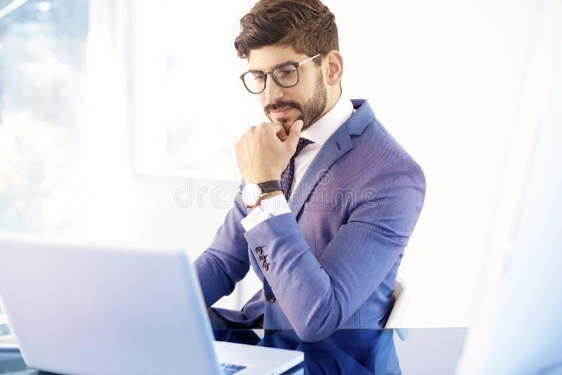 Het denken jonge zakenmanzitting achter zijn laptop terwijl worki stock afbeeldingen