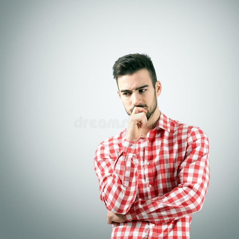Het denken maakte zich de jonge mens in plaidoverhemd ongerust stock afbeeldingen
