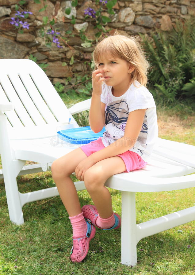 Het denken meisjeszitting op tuinlanterfanter stock fotografie