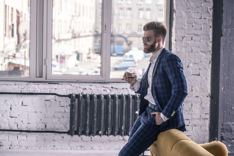 Het denken over iets De nadenkende jonge mens in volledig kostuum en de zonnebril drinken whisky en het kijken weg houdend hand o stock foto's