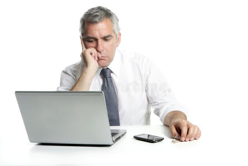 Het denken van de zakenman droevige hogere laptop computer stock foto