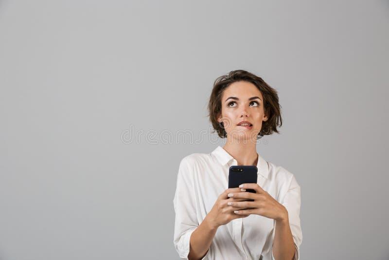 Het denken verwarde het jonge bedrijfsvrouw stellen geïsoleerd over grijze muurachtergrond gebruikend het mobiele telefoon babbel stock foto's