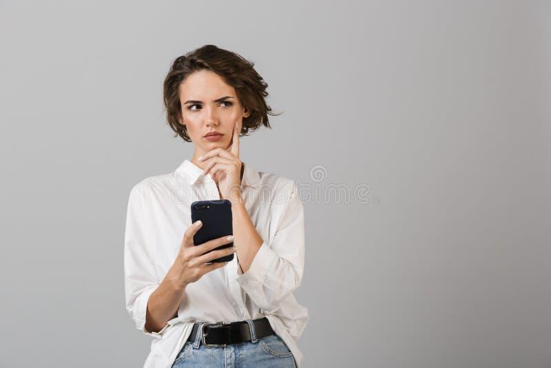 Het denken verwarde het jonge bedrijfsvrouw stellen geïsoleerd over grijze muurachtergrond gebruikend het mobiele telefoon babbel stock afbeelding
