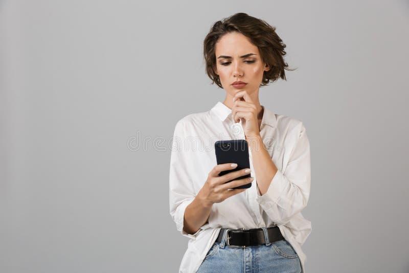 Het denken verwarde het jonge bedrijfsvrouw stellen over grijze muurachtergrond gebruikend het mobiele telefoon babbelen stock foto's