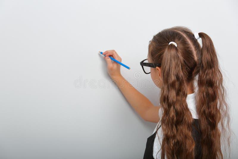Het denkende glimlachende meisje die van het leerlingsjonge geitje in oogglazen potlood trekken stock fotografie