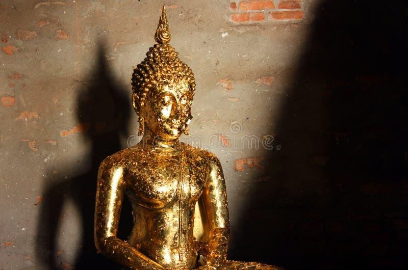 Het detail van het beeldhouwwerk van Boedha behandelde met het aanbieden van gouden bladeren in Wat Yai Chai Mongkhon, Thailand stock afbeeldingen